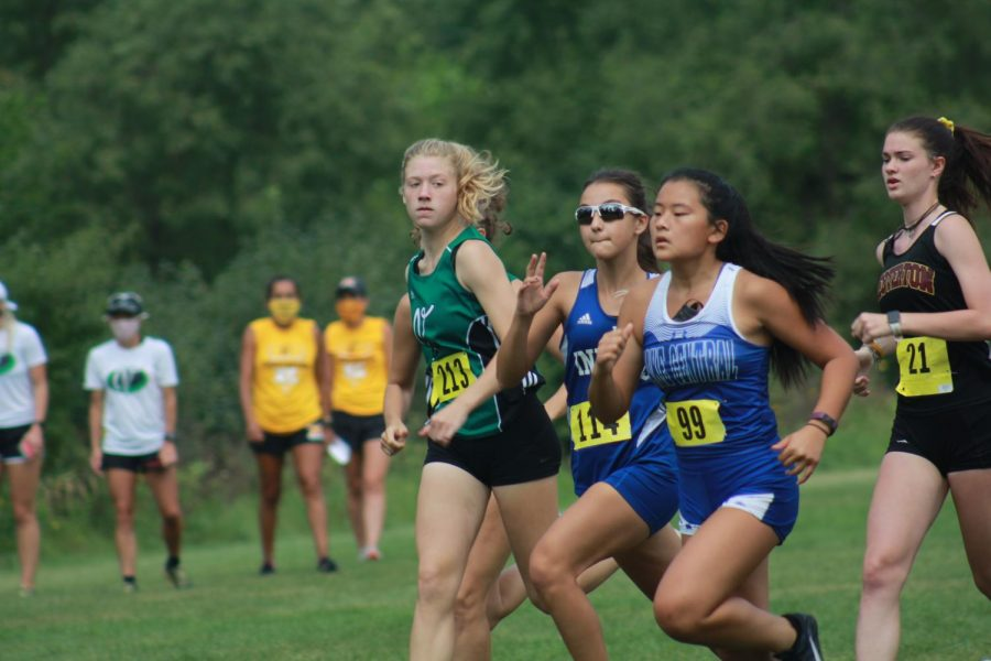 Two girls run side by side as the meet begins. The girls team practiced running through their home course to prepare for the meet.