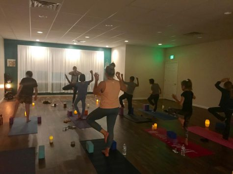 Sarah Johnson leads a yoga class from the front of the room. She walked the students through tree pose.