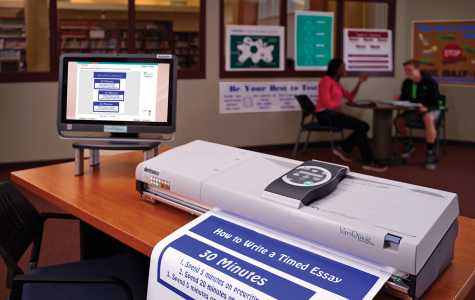 A poster exits the printer while sitting on a desk. Many posters such as these are made using printers in graphic design.
