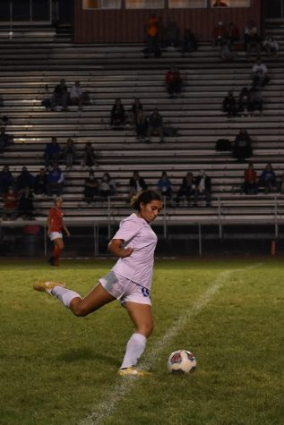 Simone Castaneda (11) kicks the ball down the field. She played an important part in keeping the ball away from their goal.