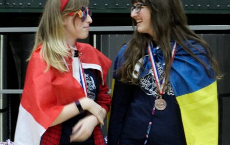 Allison Peterson (12) stands to the right of Nikki Kozel (graduated 2018-19) during a 2018 Science Olympiad competition.  The duo won third place for the Astronomy event during this meet.