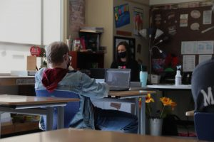 A student watches Mrs. Rokita teach virtually while guidance counselor Mrs. Rogers substitutes. Rogers had to fill in the place of the teacher in order to maintain adult supervision. Photo by: Jordan Znosko