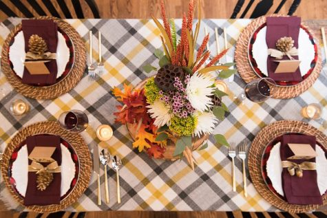 Thanksgiving table gets dressed up with fancy plates and festive decorations. Families might have to limit the amount of members at their table.