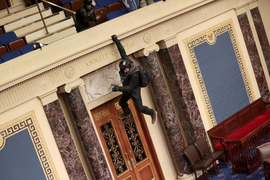 A protestor hangs from a balcony in the Senate Chamber. This was one of the pictures used by Gen Z to both spread awareness and create humor during the capitol riots. (Win McNamee/Getty Images/TNS)
