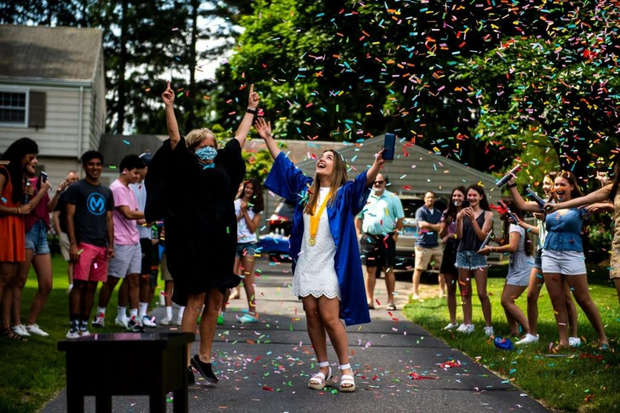 Glastonbury+High+School+graduate+Fiona+DeFranco+celebrates+with+principal+Dr.+Nancy+Bean%2C+as+DeFranco%27s+friends+pop+confetti+into+the+air+after+she+received+her+diploma+Wednesday%2C+June+10%2C+2020%2C+in+Glastonbury.+Wednesday+was+Glastonbury+High+School%27s+fifth+and+final+day+of+delivering+diplomas+to+graduates.+Each+student+got+to+wear+their+cap+and+gown+while+GHS%27s+principal%2C+Dr.+Nancy+Bean+jumped+out+of+a+decked+out+Jeep%2C+grabbed+the+diploma+from+the+decorated+bus+and+presented+the+student+with+his+or+her+diploma+in+front+of+friends+and+family+in+their+front+yards.%0A