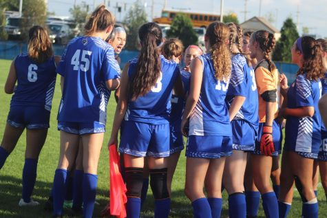 The girls huddling up right before the game starts. They were already sweating in the heat.