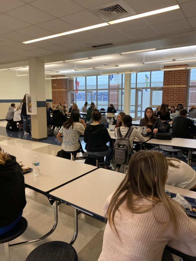 Students are sitting together at assigned lunch tables at the end of lunch. Students used to eat in classrooms instead of in the cafeteria.