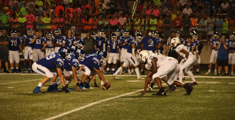 Players line up in starting positions with Lake Central in possession in the ball.   This play happened during the second quarter, some time before a touchdown near the end of the period.  Meanwhile, the student section showed overwhelming dedication to the theme of bright clothing.