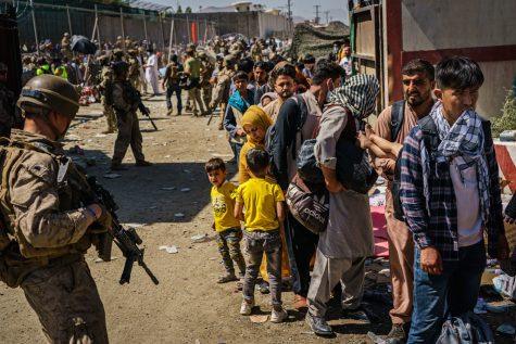 American soldiers watch over Afghan refugees waiting in line to be processed for an exit flight out of Kabul, Afghanistan, Wednesday, Aug. 25, 2021. (Marcus Yam/Los Angeles Times/TNS)