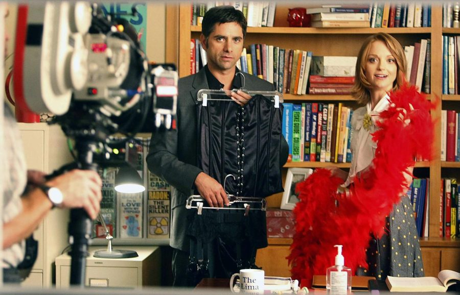 John Stamos shows Jayma Mays their Halloween costume that has a Rocky Horror Picture Show theme, during the filming of an episode of Glee in Hollywood, California.