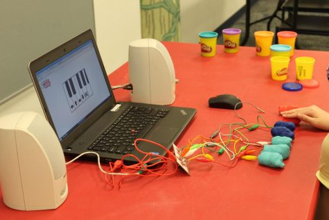 """Holding the """"ground"""" wire, members were able to complete their pianos. By pressing the Play-Doh balls, the pianos made sound through the speakers."""