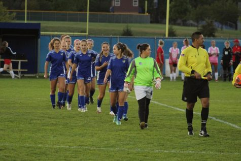 The team walks up to be introduced before the game. Freshman goalie, Olivia Pelot, led them to the introduction.